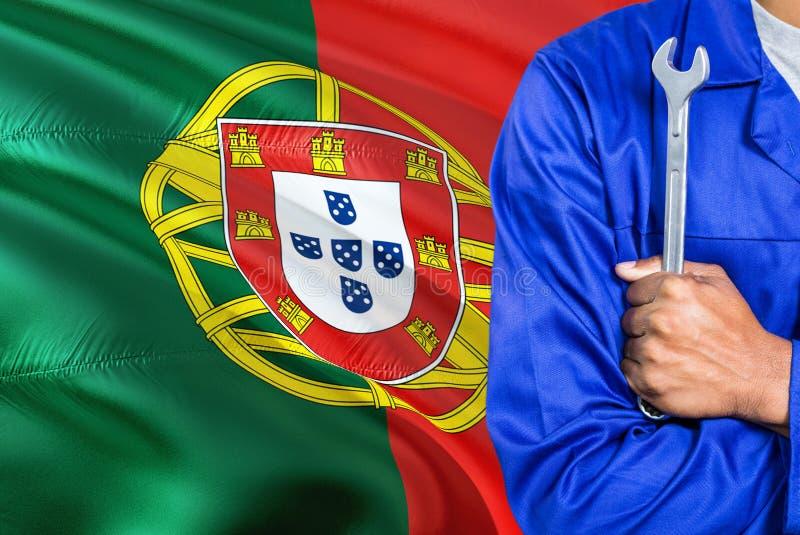 O mecânico português no uniforme azul está mantendo a chave contra a ondulação do fundo da bandeira de Portugal Técnico cruzado d foto de stock royalty free