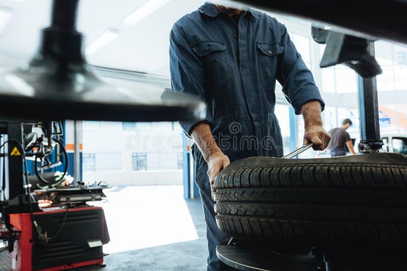 O mecânico remove o pneu de carro na garagem fotografia de stock royalty free