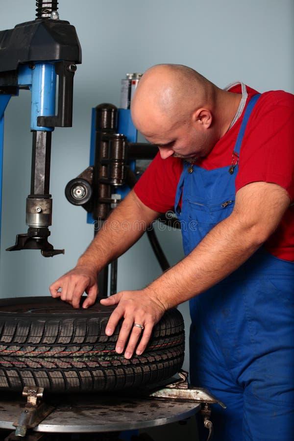 O mecânico repara o pneu fotografia de stock royalty free