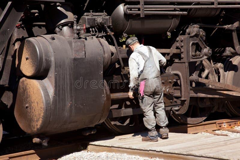 O mecânico verific a locomotiva imagens de stock