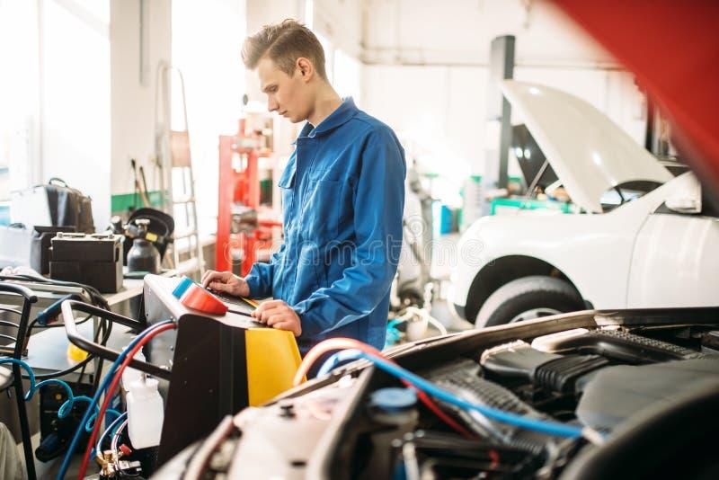 O mecânico verifica o sistema de condicionamento de ar no carro foto de stock royalty free