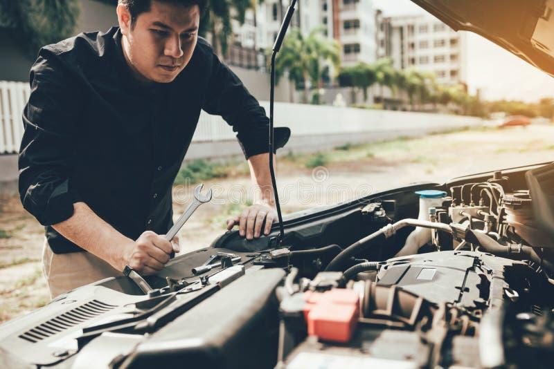 O mec?nico de carro est? mantendo uma chave pronta para verificar o motor e a manuten??o fotografia de stock