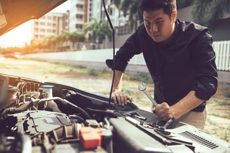 O mec?nico de carro est? mantendo uma chave pronta para verificar o motor e a manuten??o imagem de stock royalty free