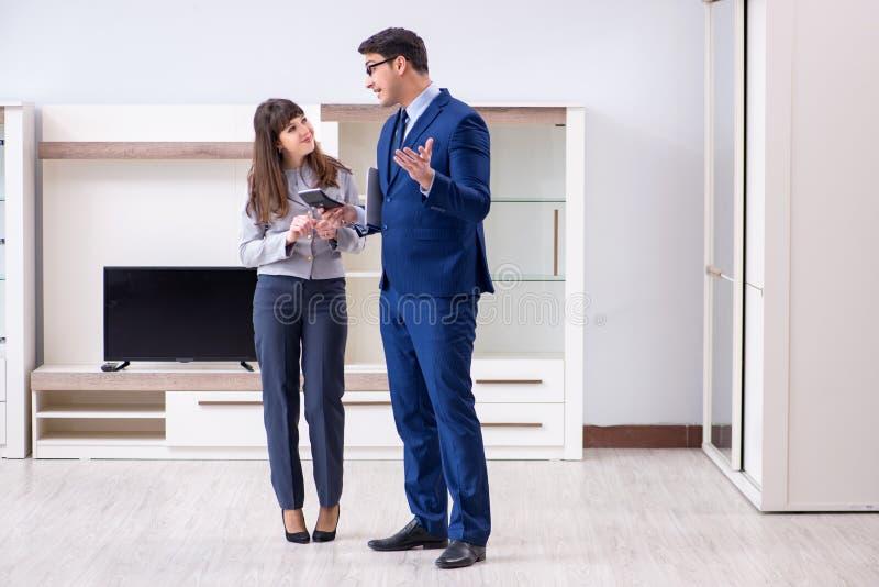 O mediador imobiliário que mostra o apartamento novo ao proprietário imagem de stock