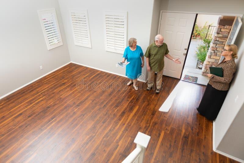 O mediador imobili?rio Showing Senior Adult acopla uma casa nova imagens de stock