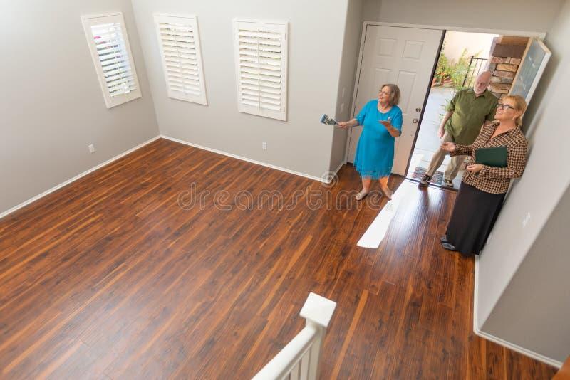 O mediador imobili?rio Showing Senior Adult acopla uma casa nova fotos de stock