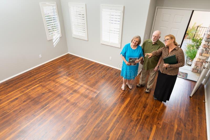 O mediador imobili?rio Showing Senior Adult acopla uma casa nova fotografia de stock royalty free