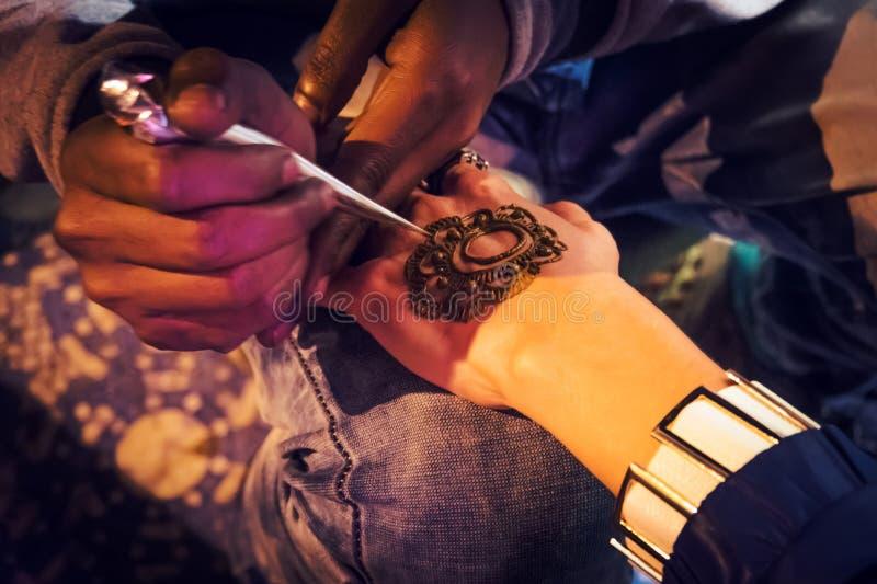 O mehndi mestre tira a hena em uma mão fêmea fotos de stock