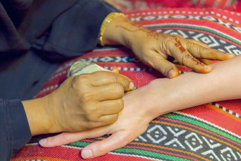 O mehndi mestre tira a hena em uma m?o f?mea imagens de stock