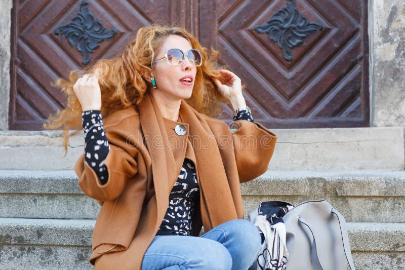 O meio atrativo envelheceu a mulher caucasiano branca com glassess vermelhos encaracolados acenados do cabelo e do sol imagens de stock