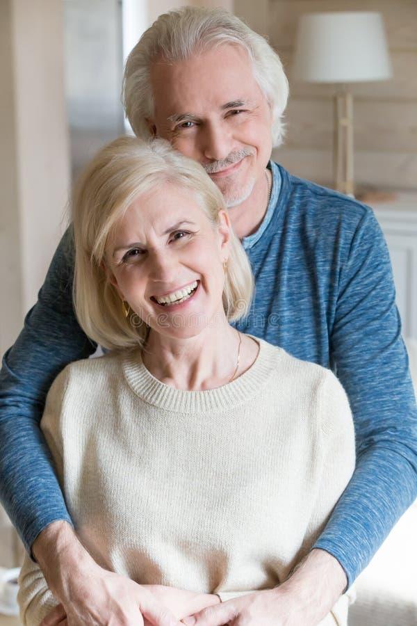O meio atrativo feliz envelheceu os esposos que levantam para a câmera fotografia de stock royalty free