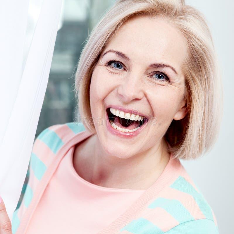 O meio bonito do retrato envelheceu o sorriso da mulher amigável e a vista na câmera fim da face da mulher acima fotos de stock