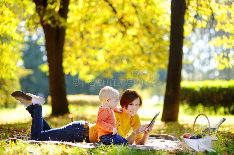 O meio bonito envelheceu a mulher e seu neto pequeno adorável que têm um piquenique no parque ensolarado foto de stock royalty free