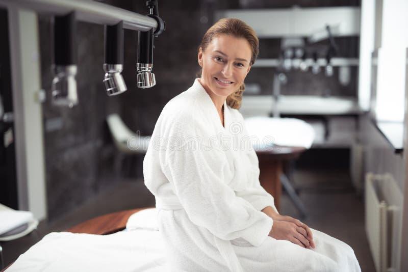 O meio bonito envelheceu a mulher que senta-se na tabela da massagem fotos de stock