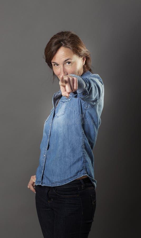 O meio bonito presumido envelheceu a mulher que aponta seu dedo para a frente foto de stock