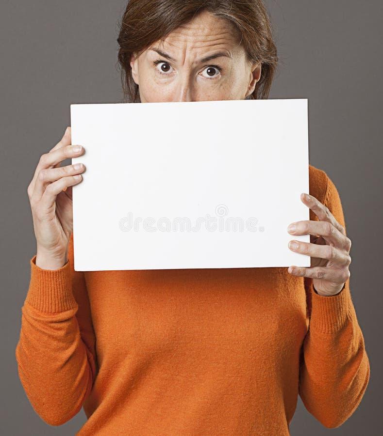 O meio crítico envelheceu a mulher que esconde atrás da placa de comunicação vazia assustador fotos de stock royalty free