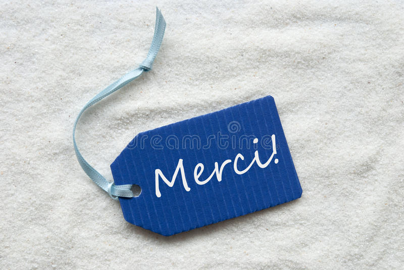O meio de Merci agradece-lhe no fundo azul da areia da etiqueta fotos de stock royalty free