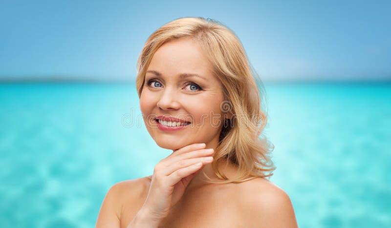 O meio de sorriso envelheceu cara tocante da mulher sobre o mar imagens de stock royalty free