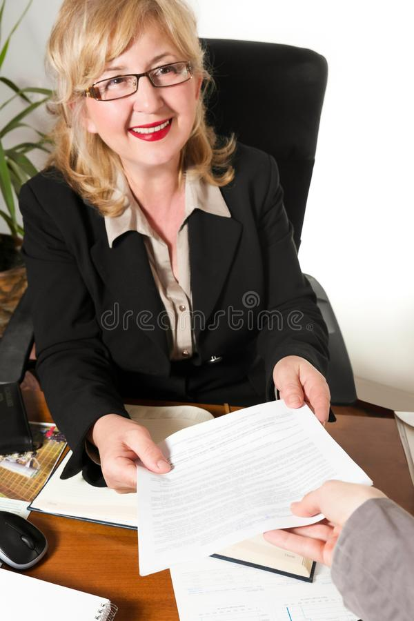 O meio de sorriso envelheceu a mulher de negócios, com original em suas mãos. imagem de stock royalty free
