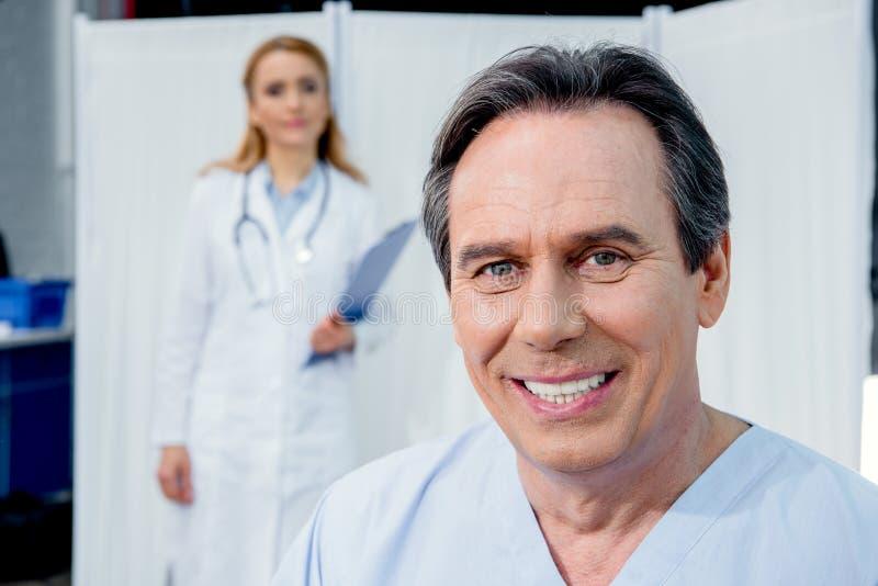 O meio de sorriso envelheceu o paciente com doutor atrás no hospital imagens de stock royalty free