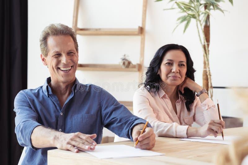 O meio de sorriso envelheceu os colegas que fazem anotações na reunião de negócios fotografia de stock
