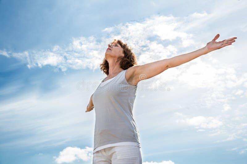 O meio do zen envelheceu a mulher da ioga que abre seu chakra imagens de stock royalty free