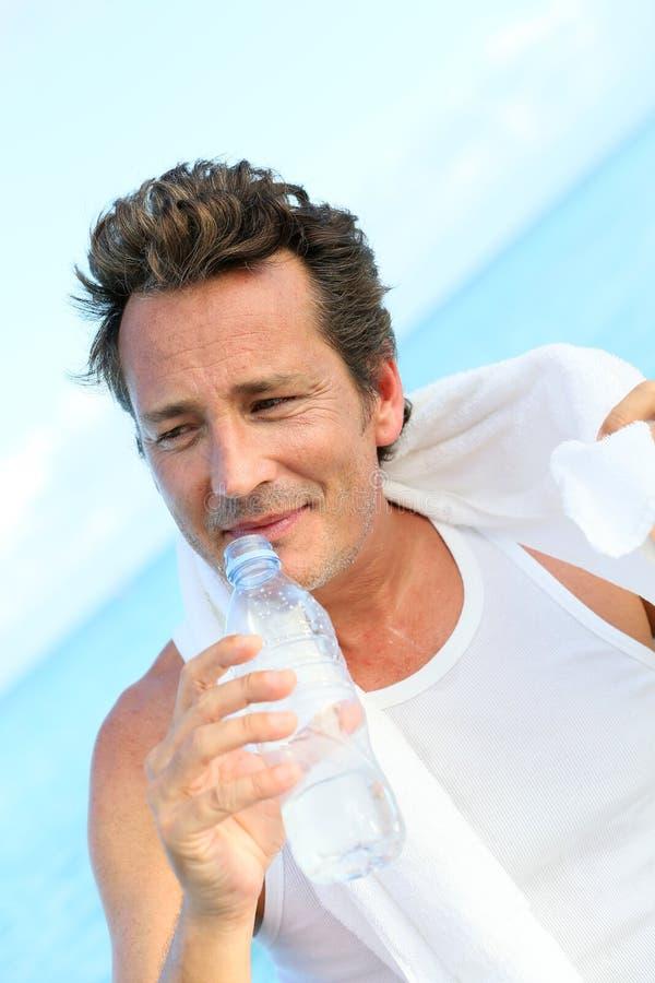 O meio envelheceu a água potável do homem após excersising pelo mar foto de stock