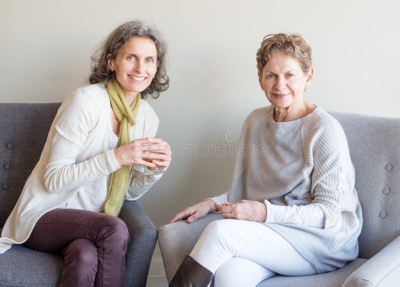 O meio envelheceu a filha no lenço verde que sorri ao lado de uma mãe mais idosa fotografia de stock