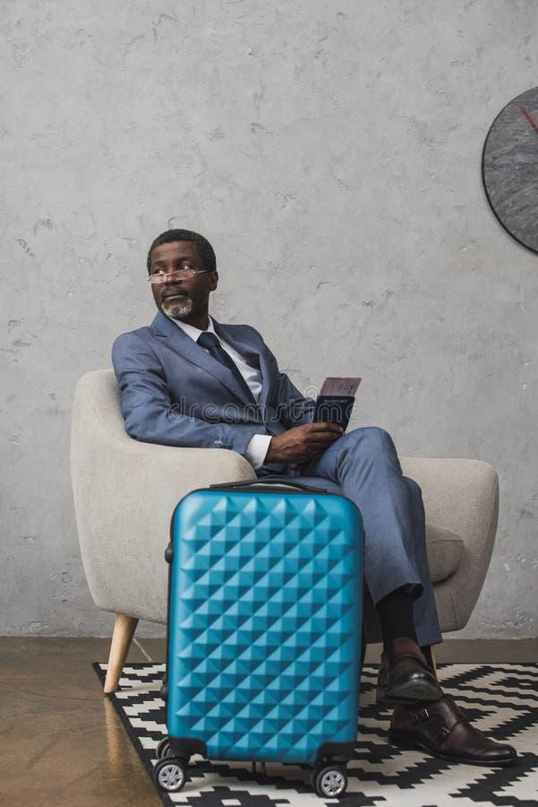 O meio envelheceu o homem de negócios que senta-se em uma poltrona e que guarda o passaporte foto de stock