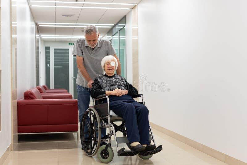 O meio envelheceu o homem que ajuda e que toma às pessoas idosas 95 anos de mulher adulta que senta-se na cadeira de rodas foto de stock