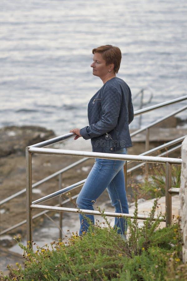 O meio envelheceu a mulher caucasiano que olha pensativamente no mar foto de stock