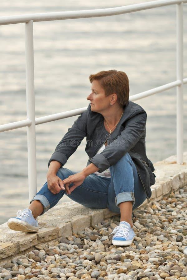 O meio envelheceu a mulher caucasiano que senta-se na praia do mar fotos de stock royalty free