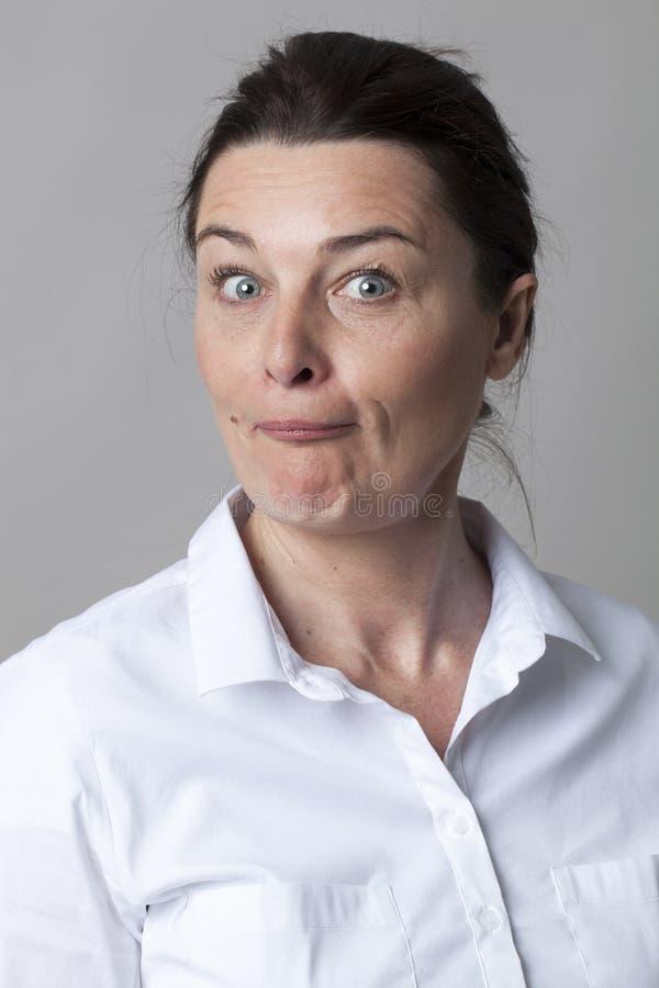 O meio envelheceu a mulher com a camisa branca esperta que questiona para o divertimento fotografia de stock royalty free
