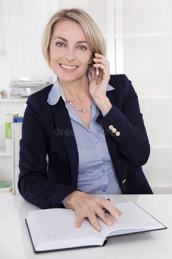 O meio envelheceu a mulher de negócio em seu escritório que chama com pho móvel imagens de stock