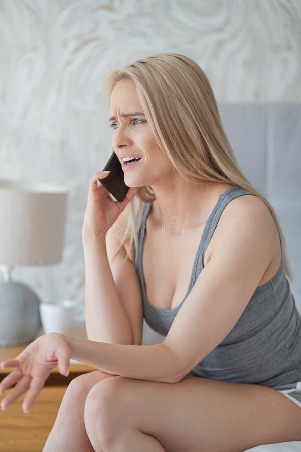 O meio envelheceu a mulher loura que senta-se em sua cama da casa e que discute com o alguém imagem de stock
