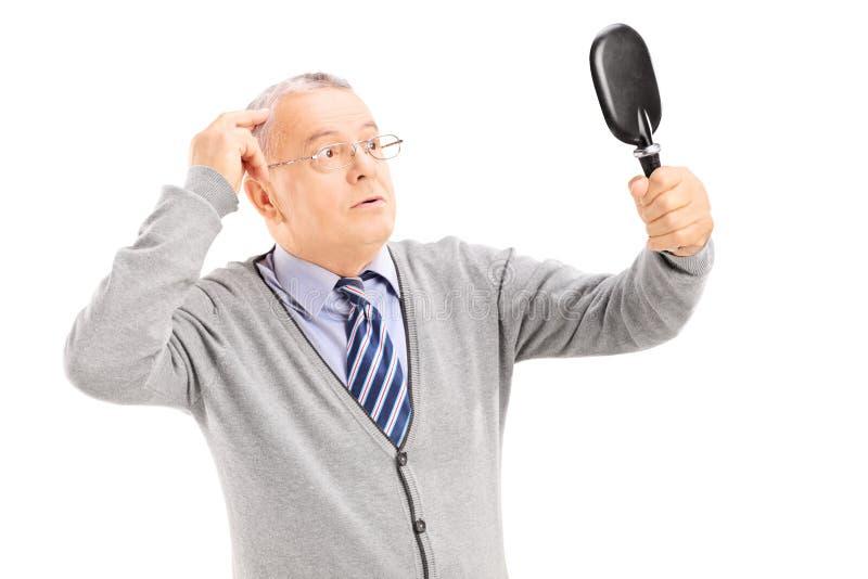 O meio envelheceu o cavalheiro que verifica para ver se há o cabelo de diluição no espelho fotografia de stock