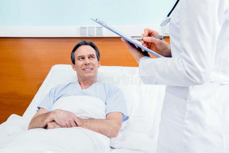 O meio envelheceu o paciente que encontra-se na cama e no doutor com o diagnóstico que está perto dele fotos de stock royalty free