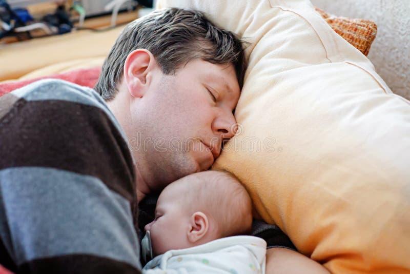 O meio envelheceu o pai que dorme perto de sua filha recém-nascida do bebê fotos de stock