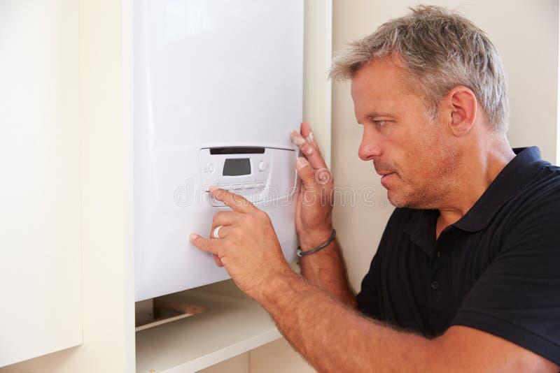 O meio envelheceu o técnico da caldeira que presta serviços de manutenção a uma caldeira doméstica fotos de stock royalty free
