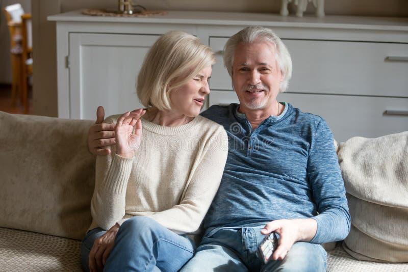 O meio envelheceu os esposos atrativos que olham a tevê sentar-se no sofá fotos de stock