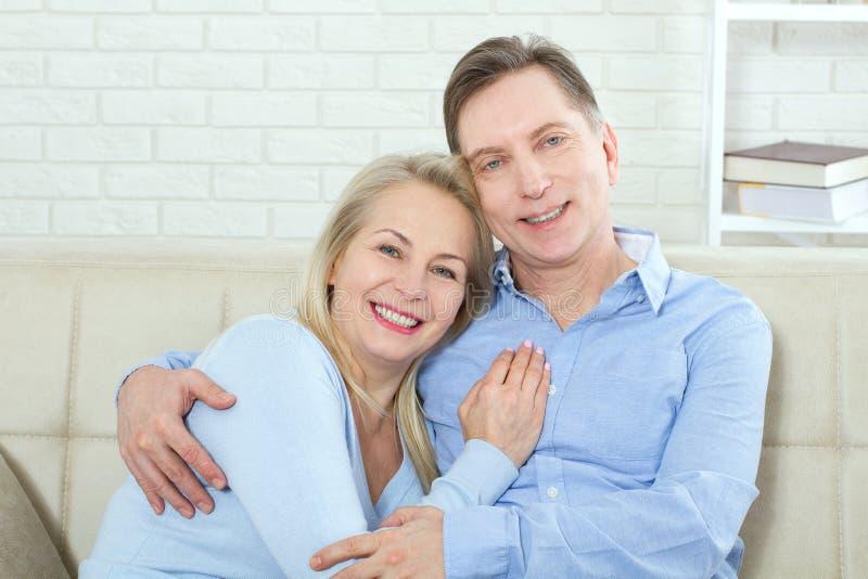 O meio envelheceu os pares que relaxam no sofá que sorri na câmera em casa na sala de visitas foto de stock