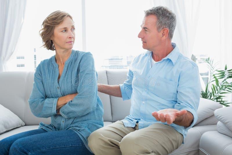 O meio envelheceu os pares que sentam-se no sofá que tem uma disputa imagem de stock royalty free