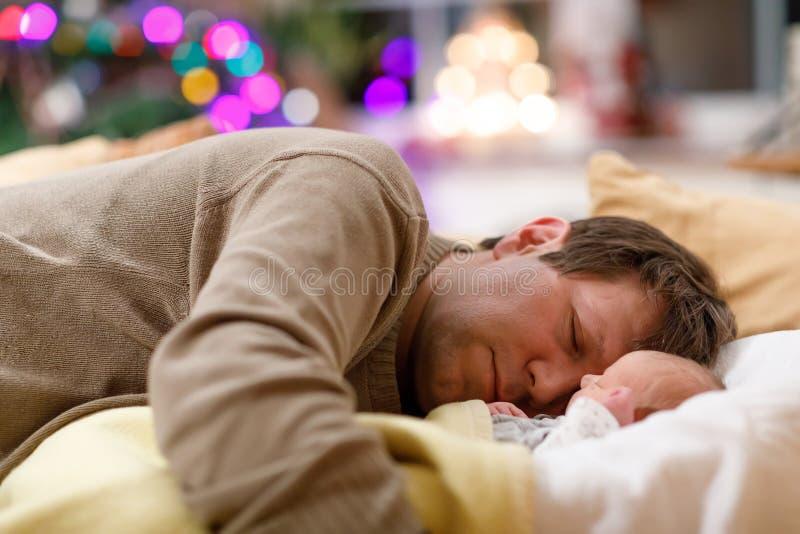 O meio envelheceu o pai que dorme perto de sua filha recém-nascida do bebê no Natal foto de stock