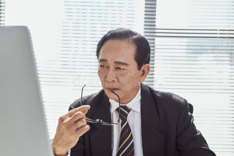 O meio envelheceu o sentimento asiático do homem de negócios forçado e frustrado ao trabalhar na estação de trabalho Conceito do  fotografia de stock
