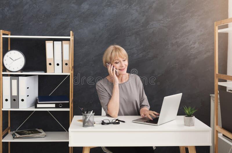 O meio feliz envelheceu a mulher de negócios no trabalho que fala no telefone imagem de stock royalty free