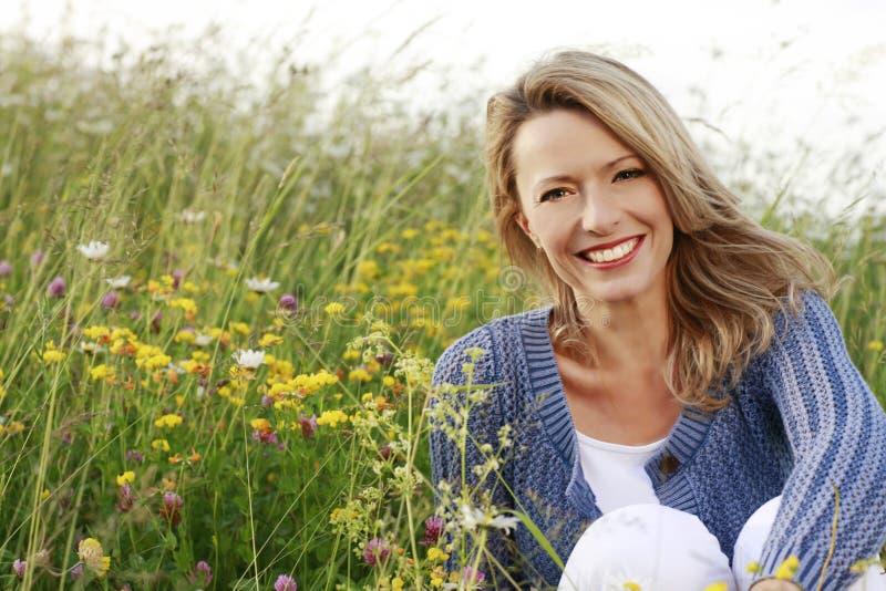 O meio feliz envelheceu a mulher no campo de flor selvagem fotos de stock