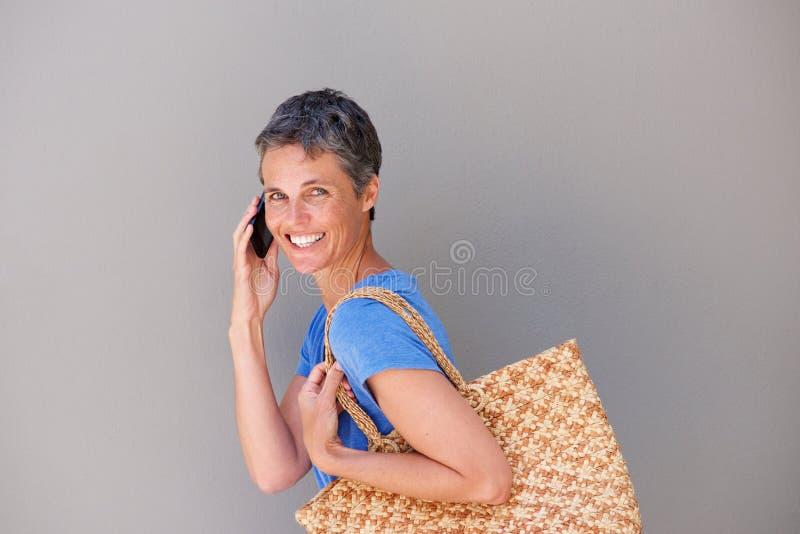 O meio feliz envelheceu a mulher que anda e que fala no telefone celular imagem de stock