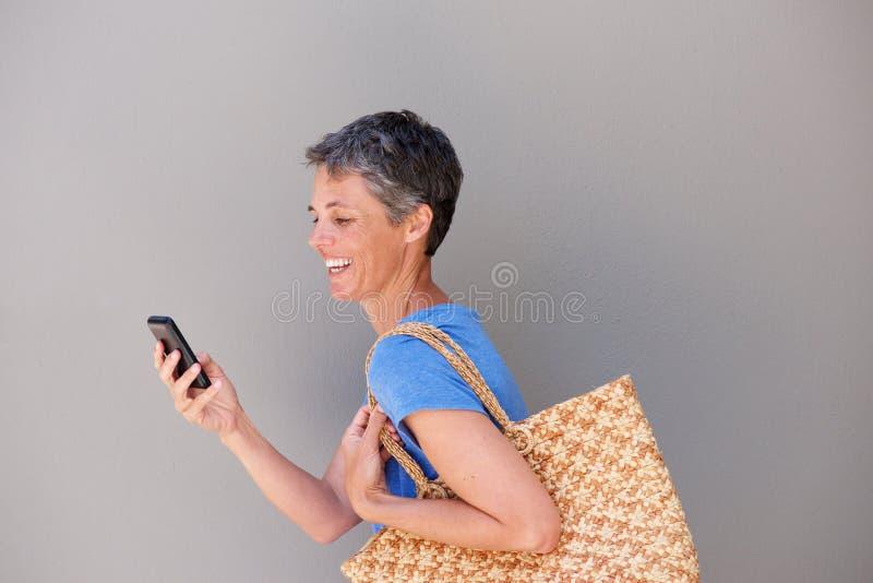 O meio feliz envelheceu a mulher que anda e que olha o telefone celular fotos de stock