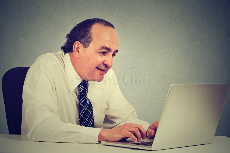 O meio feliz envelheceu o homem de negócios que trabalha com o portátil no escritório imagens de stock