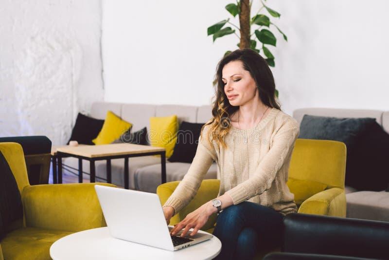 O meio novo envelheceu a mulher caucasiano com cabelo longo Roupa ocasional usando o laptop dentro Restaurante do café na cadeira imagens de stock